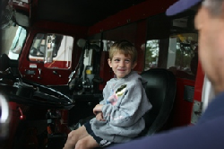 young boy in a fire truck talking with a firefighter