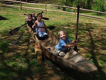 Three children in a canoe in the park