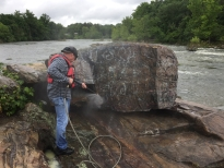 Officer Young cleaning up graffiti from rocks on the river